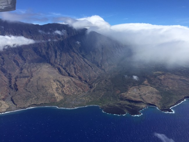 South-eastern shoreline of Maui near Kaupo, showing orographic lifting of moist air in the tradewind flow by the flanks of Haleakala and resulting in cloud build-up and precipitation. Notice the difference in vegetation closer to the windward side of the island as a result.